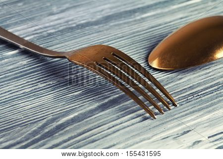 Gold spoon and fork on the gray wooden background. vintage tableware with scratches and scrapes. Soft focus. macro