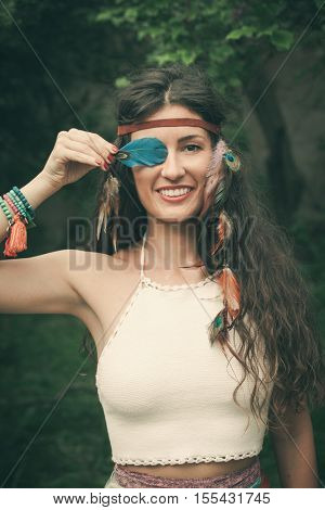 smiling young bohemian fashion style woman with feather portrait closeup