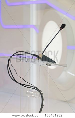 Modern conference podium with microphone on glass stand