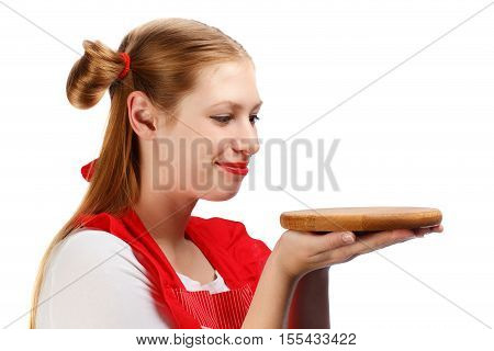 Young beautiful smiling housewife in bright red apron with funny ponytails holding wooden cutting board isolated on white background. Close up.