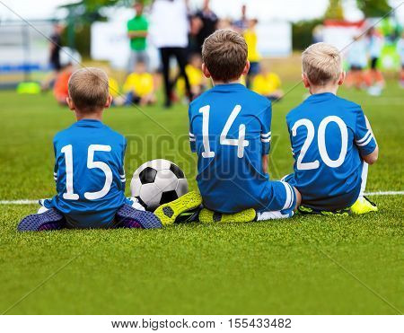 Children In Blue Sportswear Sitting On Soccer Pitch And Watching Football Soccer Match. Kids Soccer Tournament. Youth Soccer Background