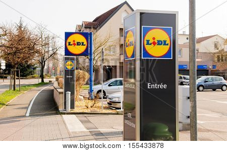 STRASBOURG FRANCE - MAR 20 2016: Lidl supermerket entrance with trolleys cars in parking on a sping day