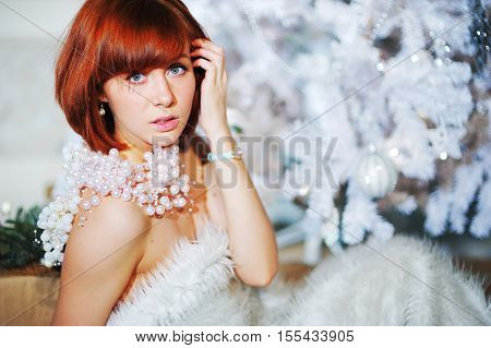 Young charming girl with bright brown hair in a white fur Cape sits around the Christmas tree