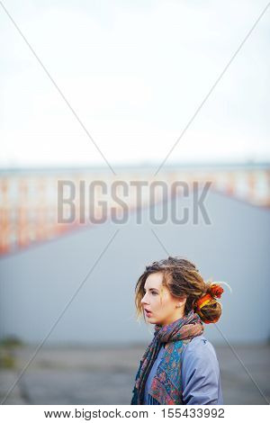Portrait of young beautiful girl with dreads in a scarf and coat on a blurred background of the town square