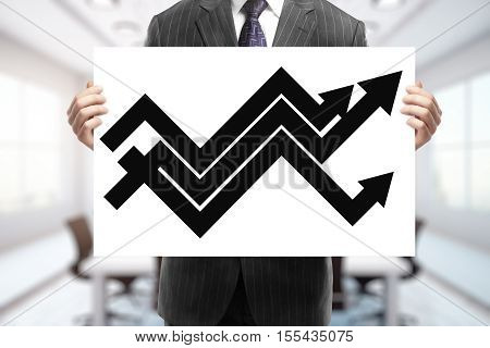 Businessman holding poster with upward chart arrows. Success concept