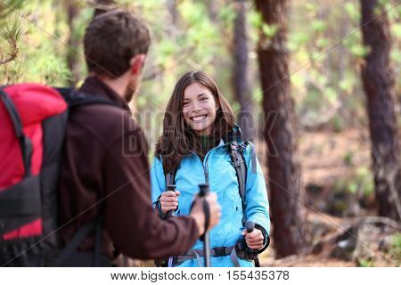 Happy young hikers friends having fun talking together during forest hike in mountains. People hiking with hiking poles and backpacks in nature, outdoor lifestyle. Asian woman, Caucasian man.