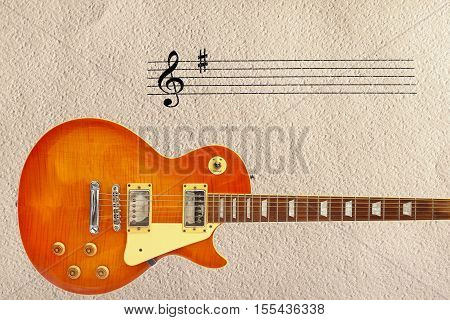 Notes stave and honey sunburst vintage electric guitar at the bottom of the rough cardboard background.
