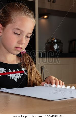 Young girl doing homework at home at the kitchen table holding a pencil