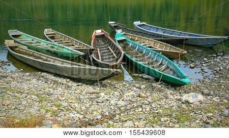 Old wooden boats moored to the bank of the river. Beautiful river landscape.