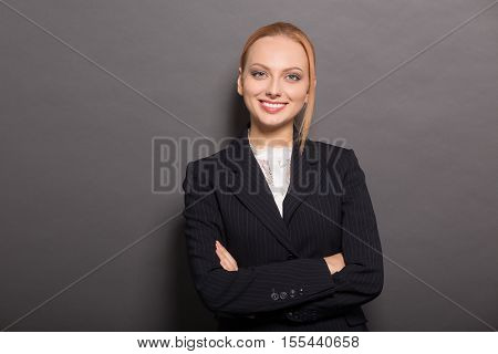 Portrait of happy smiling business woman smiling for camera with her arms crossed or folded while posing for photographer in studio.