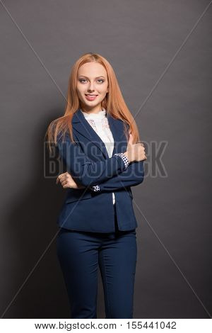 Picture of confident business woman smiling with her arms crossed or folded isolated on grey background in studio. Business concept.