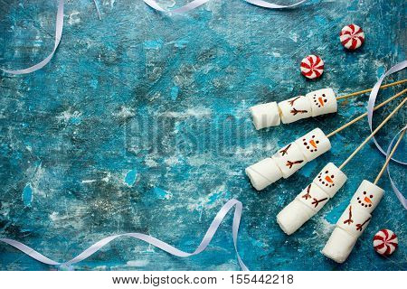 Christmas blue background - sweet treat for kids funny marshmallow snowman top view blank space for text