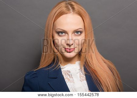 Closeup portrait of happy smiling model woman with red hair looking at camera while posing for photographer isolated on grey background in studio.
