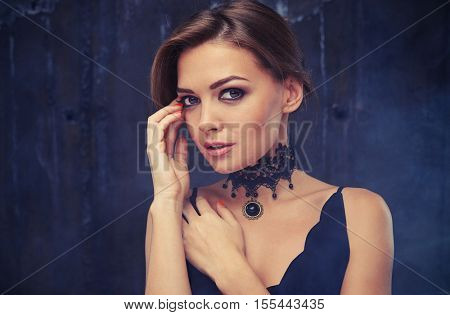 Close-up beauty fashion portrait of Caucasian brunette woman touching face and her appearance in the smoke. Beauty portrait, head and shoulders, studio, indoor