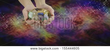 Crystal Therapy Website Banner - female crystal therapist holding and offering a brass dish containing a selection of crystals on a wide vibrant multicolored background and a stream of delicate sparkles