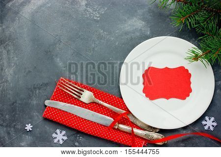 Christmas table place setting with vintage silverware on red napkin white plate and empty greeting card. Christmas holidays background