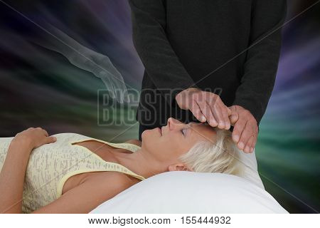 Spirit Guide Assisting Healing Session -  male healer channeling healing energy to supine resting female with the transparent hand of a spirit healing guide floating above heart chakra
