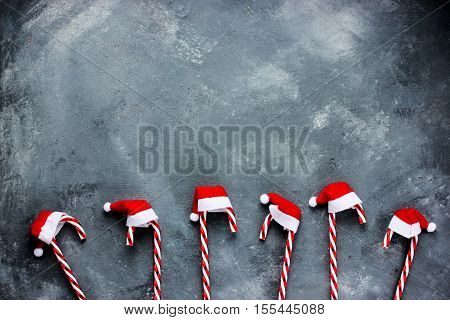 Christmas background with candy cane in santa hat blank space on a gray grunge background