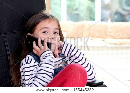 Cute Little Girl On Cell Phone Looking At Camera