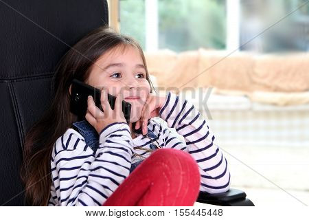 Cute Little Girl On Mobile Phone Listening And Smiling