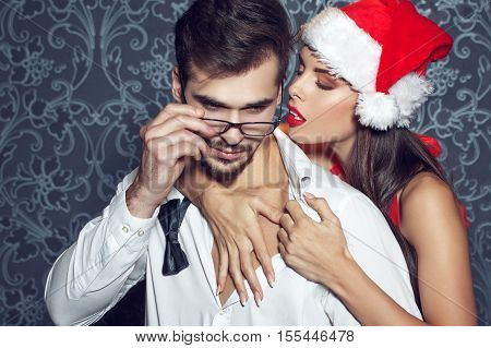 Sexy santa woman seduce young man in tux at Christmas