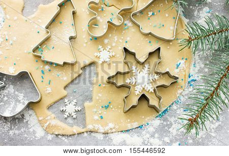 Raw dough for Christmas cookies and cookie cutters shaped glove Christmas tree snowflake jingle bell gingerbread man top view
