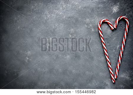 Candy cane heart on gray concrete background top view empty space for text