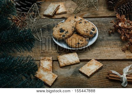 Chocolate cookies in a white plate on wooden background. Near cones and cinnamon stick, roughly. View from above. The theme of the new year holiday