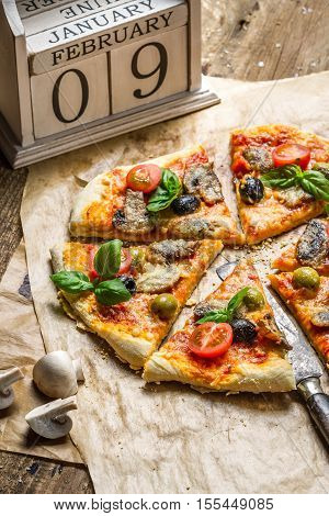 Freshly baked homemade pizza on old wooden table