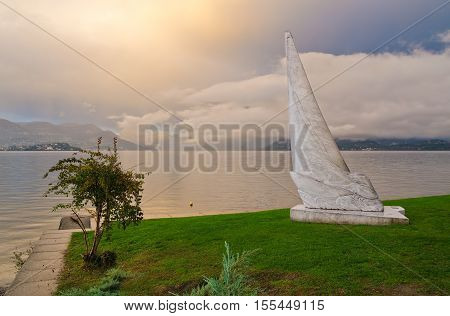 STRESA, ITALY. 26th October 2016. One of the three modern white carrara marble sculptures on Stresa's lakeside stands sentinel over Lake Maggiore at sunset.
