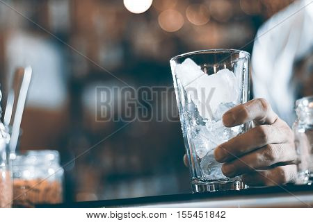 Glass With Ice Cubes On The Background Of The Bar