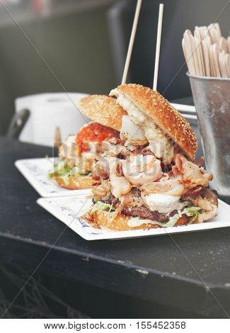 Street food burger with seafood bacon meat vegetables and mayonnaise. Street food or unhealthy food concept. Vintage tone