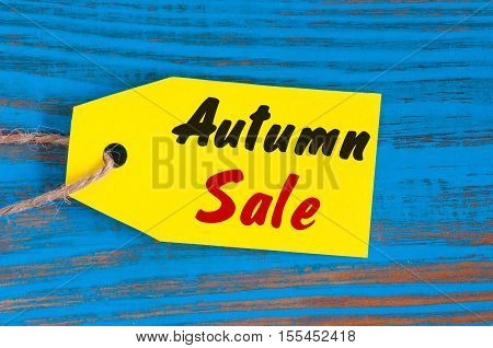 Autumn Sale, price tag on blue wooden background.
