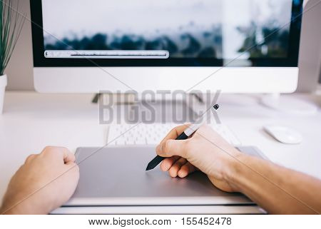 Young worker sitting in an office at the computer. Freelancer in a blue shirt. The designer sits in front of a window in the workplace. shot of screen. Space for your text or logo. Two hands on shot