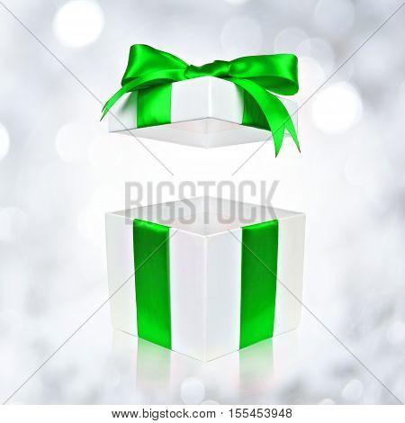 Opened White Gift Box With Green Satin Bow On A Twinkling Silver Background