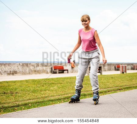 Active young woman in training suit rollerskating outdoor. Happy girl riding enjoying sport.