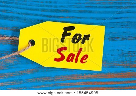 For Sale tag on blue wooden background. Sales, discount, advertising, marketing price tags for clothes, furnishings, cars