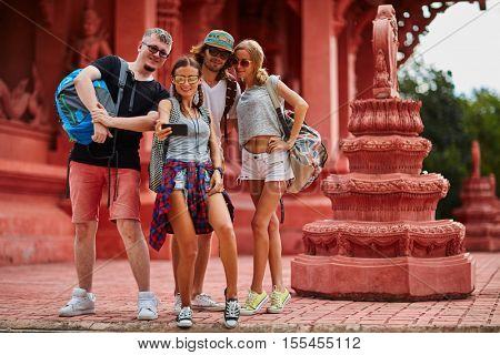 group of european tourists taking group selfie at buddhist temple in thailand