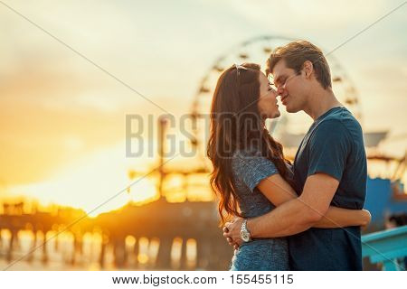 romantic couple about to kiss at sunset