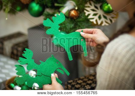 the girl holds in hand a Christmas decor of green deer