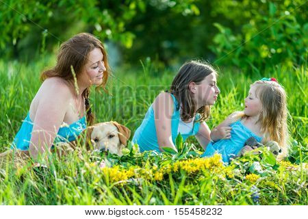 mom with two daughters and dog in the garden