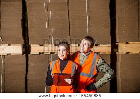 Paper mill factory workers standing near piles of cardboards