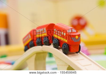 Red wooden toy train crossing the bridge (selective focus)
