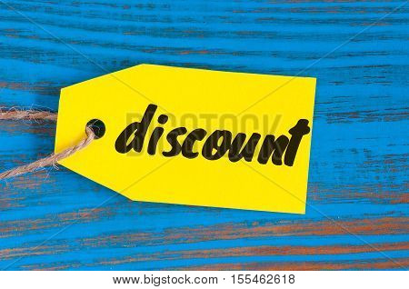 Discount percent tag label yellow color on blue wooden background.