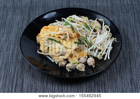 "Fried oyster with bean sprouts and shallot as ""Hoi Tod"" in Thai served with chili sauce is popular seafood in street food and restaurant."