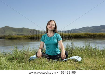 Young woman is practicing yoga at mountain river, relax in nature