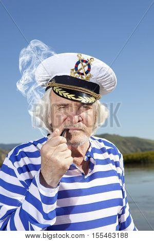Captain smokes a pipe. Sailor man