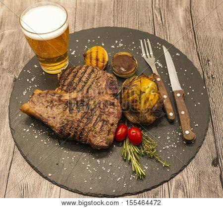 On wooden table background juicy beef steak with a glass of light beer foam