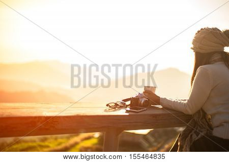 Woman drinking coffee in sun sitting outdoor in sunshine light enjoying her morning coffee, vintage, soft and focus