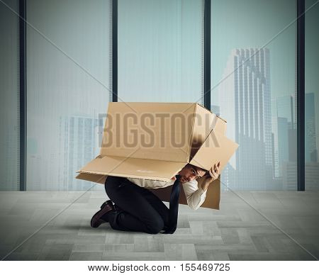 Afraid businessman is hiding under a cardboard